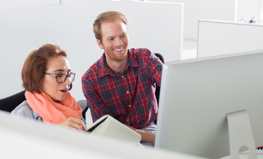 man and woman using Academy LMS on desktop computer